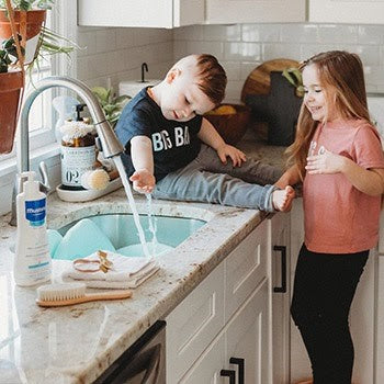 siblings washing hands together