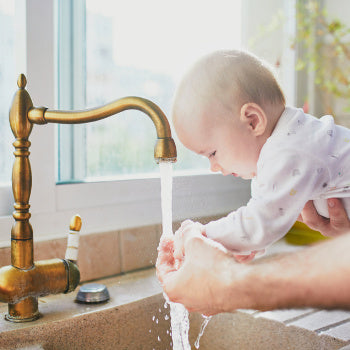 parent helping baby with hand washing