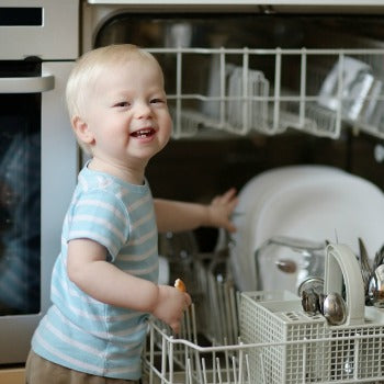 Todller helping load the dishwasher