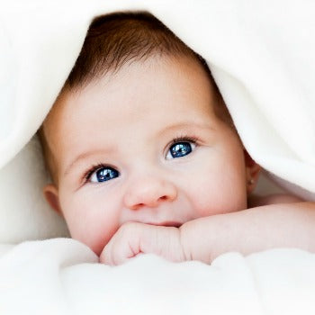 content baby peeking out from under a blanket that is draped over her head