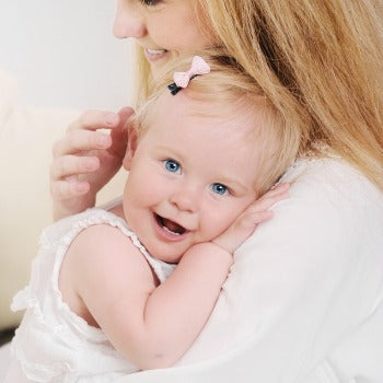 side view of mother holding smiling baby girl closely