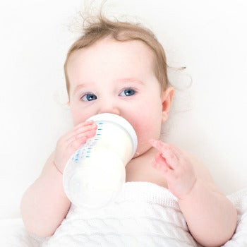 baby drinking from a bottle during newborn feeding schedule time