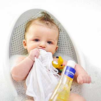 baby lying in baby bathtub with toys