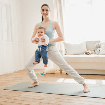 Mom doing postpartum exercise with baby