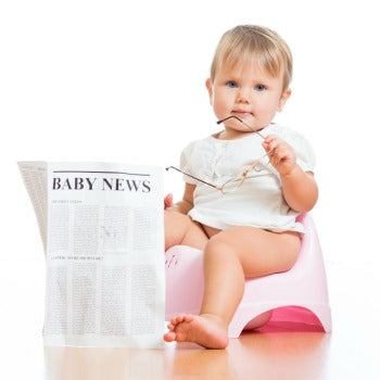 toddler sitting on pink potty holding glasses and a newspaper