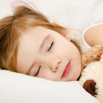 young girl sleeping on her side next to stuffed animal