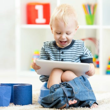 toddler giggling at tablet while sitting on potty chair