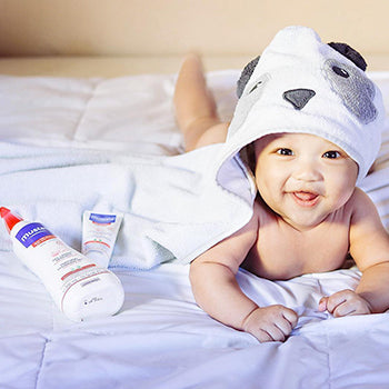 baby in hooded towel lying on tummy next to Mustela bath products