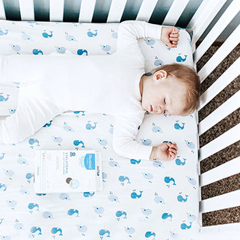 baby sleeping on their back in a crib