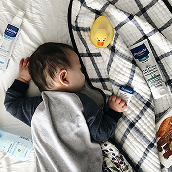 baby sleeping on tummy on black and white blanket near Mustela products