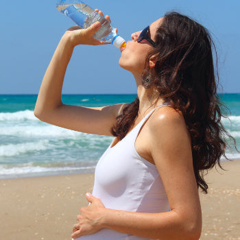 Woman staying hydrated during sunbathing while pregnant