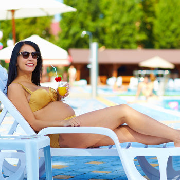 Woman out at the pool sunbathing while pregnant
