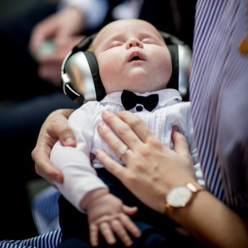 parent soothing and protecting baby's ears with a headset while traveling with baby