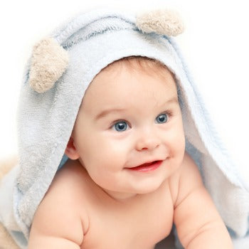 baby in hooded towel before wet wrapping therapy