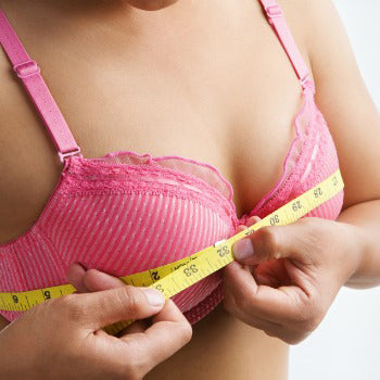 Woman measuring her breasts during first trimester