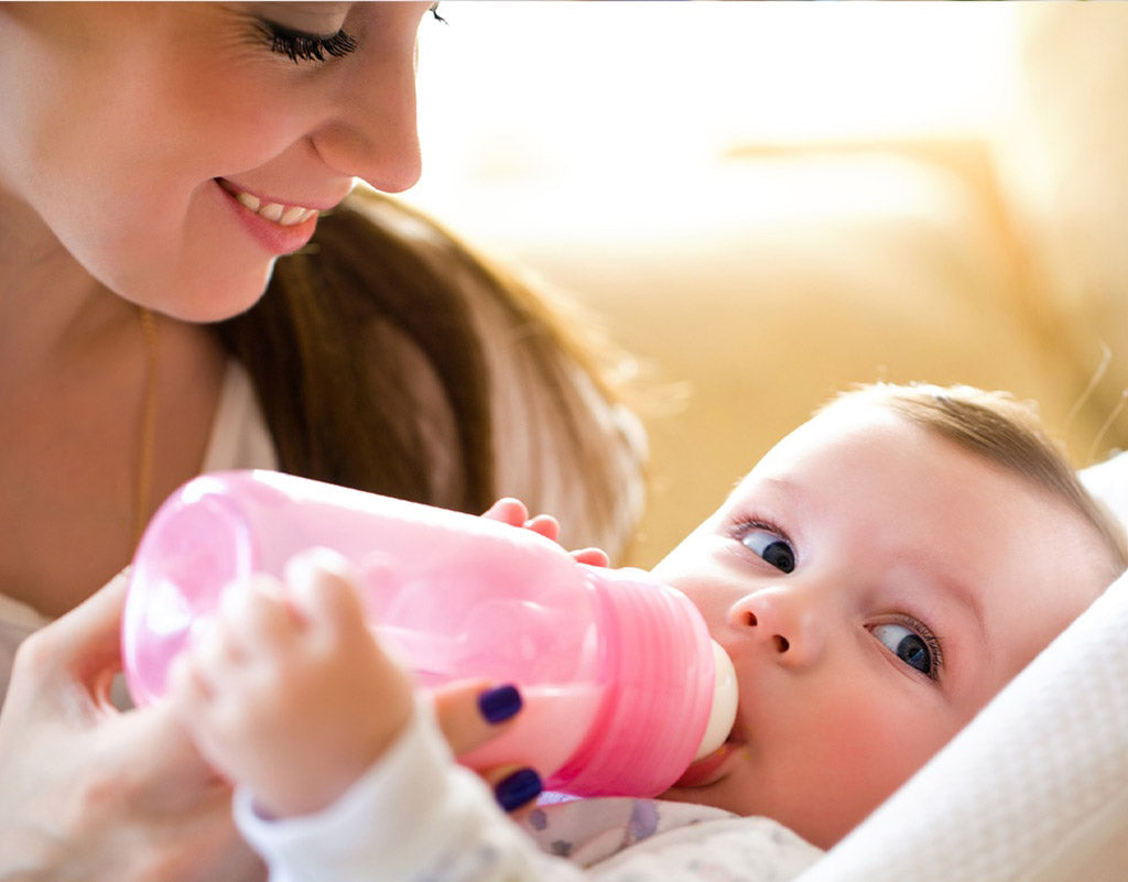 Mom holding bottle while baby is eating