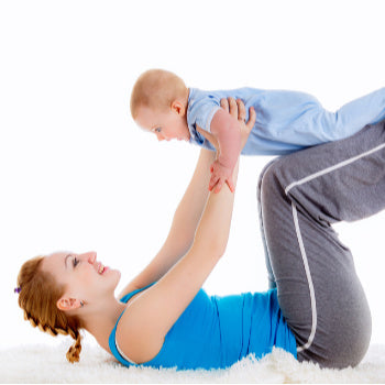Mom lifting exercising with baby to tighten loose skin after pregnancy