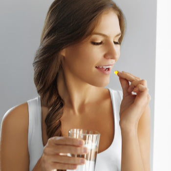 Woman taking a Collagen Supplement  to help with loose skin after pregnancy