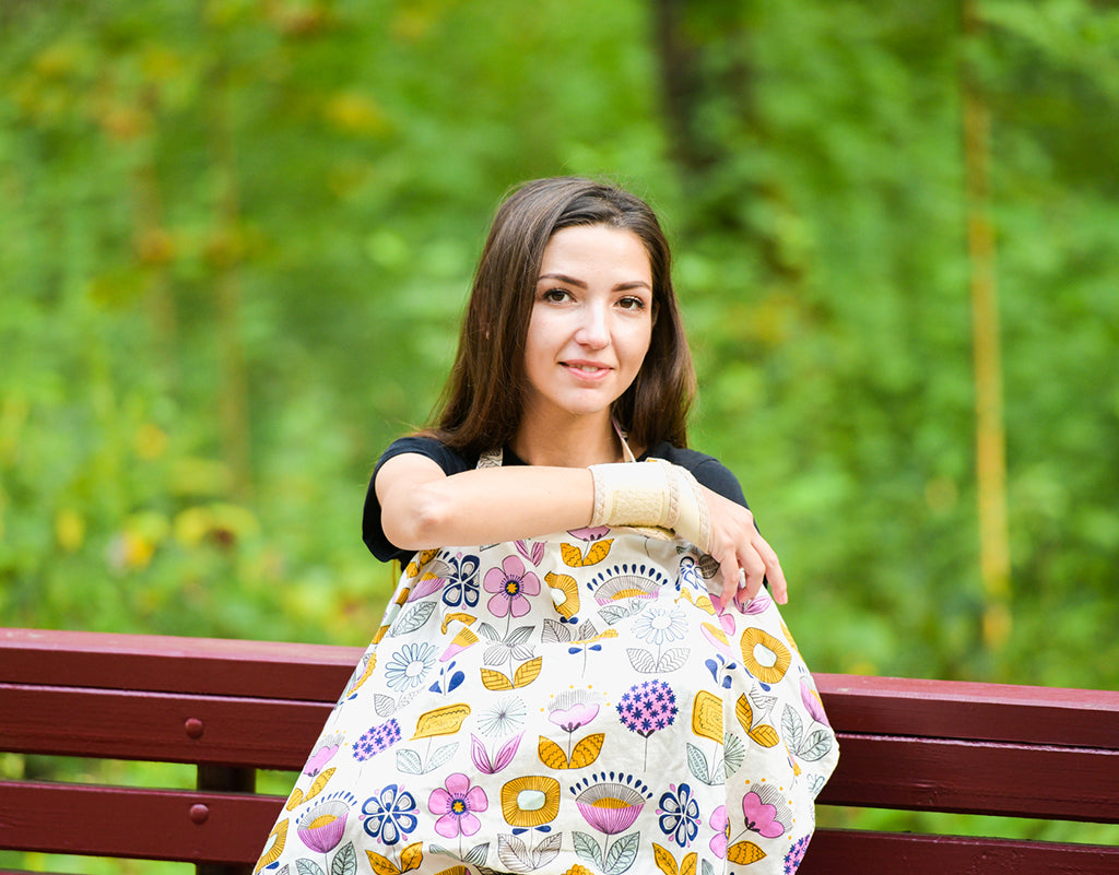 Mom using a nursing cover which is a newborn must-haves