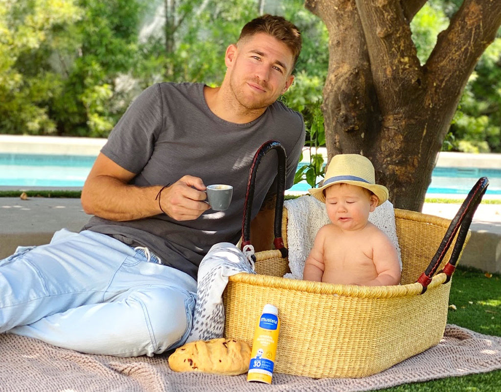 Dad on a picnic with child while being prepared with Mustela's SPF 30 Mineral Sunscreen Spray