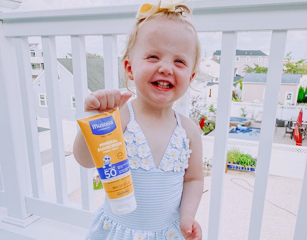 Child holding Mustela's SPF 50 Mineral Sunscreen Lotion that is non-nano zinc oxide