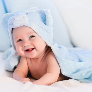 Happy baby laying with bath towel robe