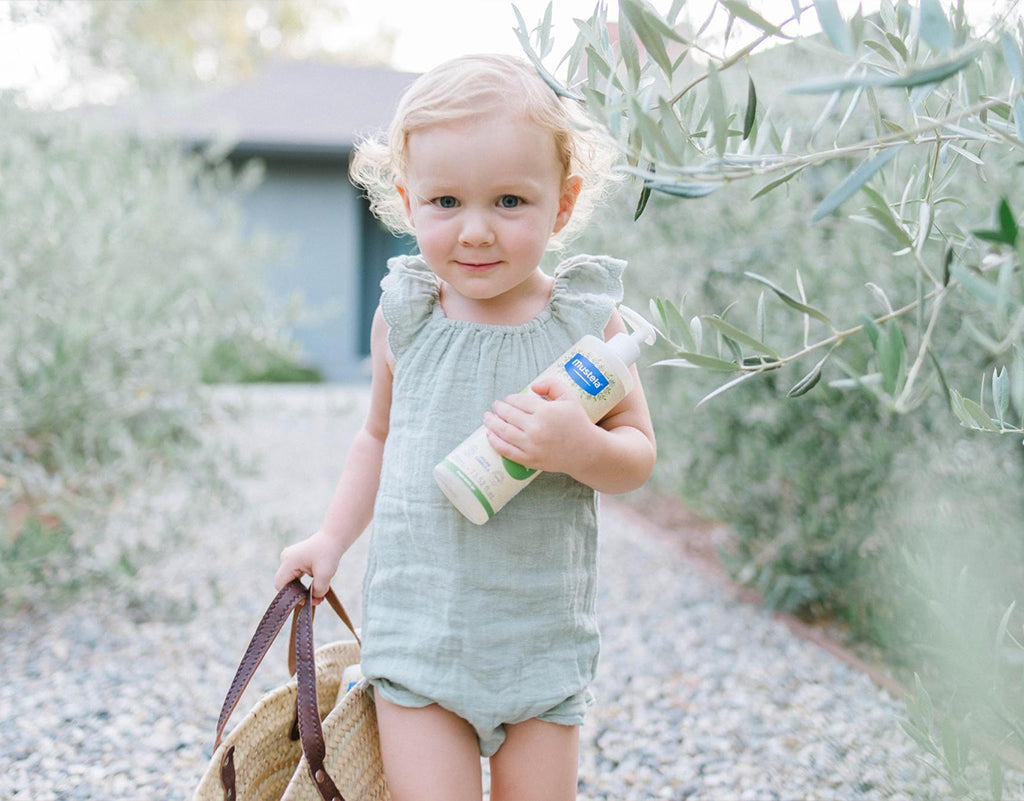 Little girl holding purse and mustela products that have Olive Oil For Skin