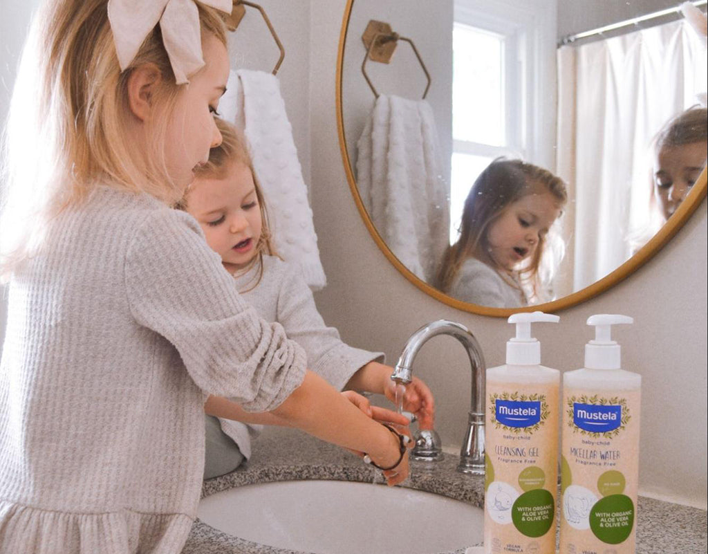 Two siblings washing their hands with mustela products