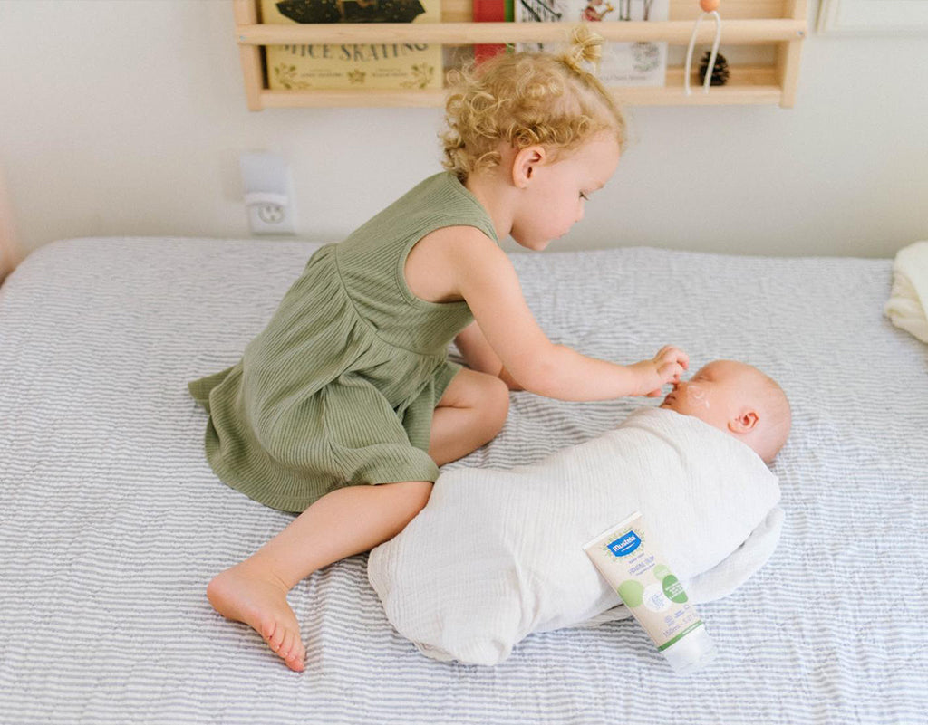 Sibling putting Mustela organic baby products on baby