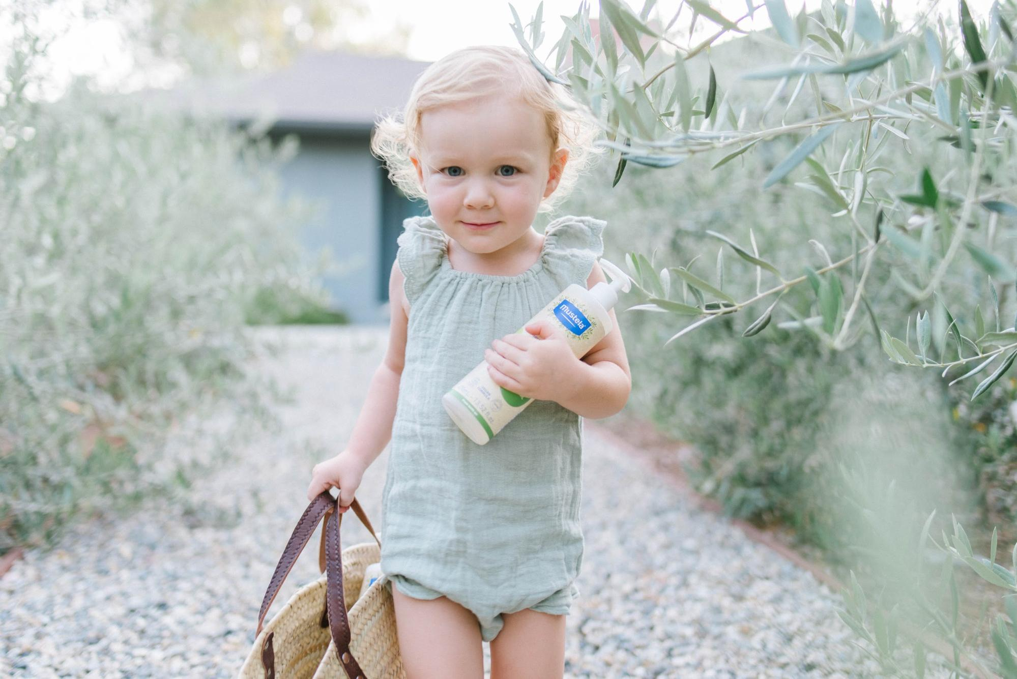 Baby holding natural skincare products
