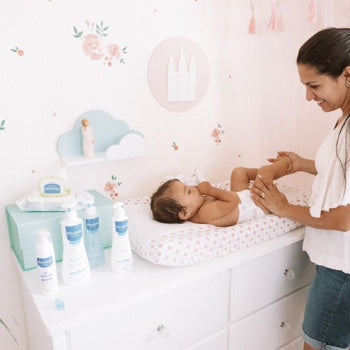 Mom changing baby diaper with paraben free products