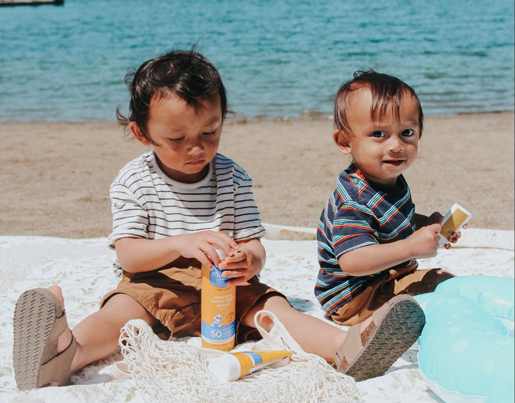 Two kids at the beach protected by Mustela Sun Products