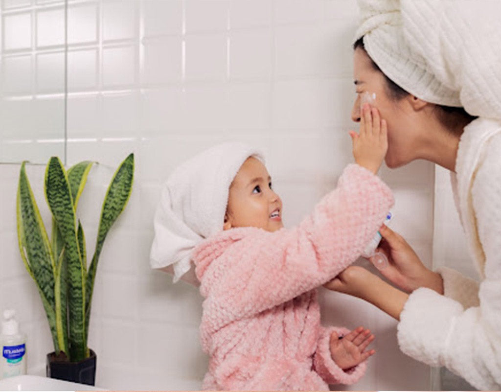 Daughter applying face cream to mom's face