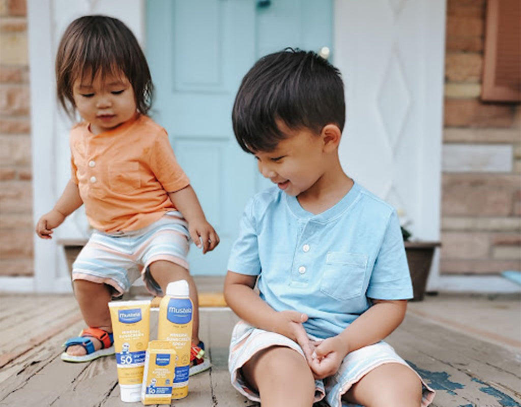 Two kids with Mustela Sun products that help prevent a red cheeks toddler