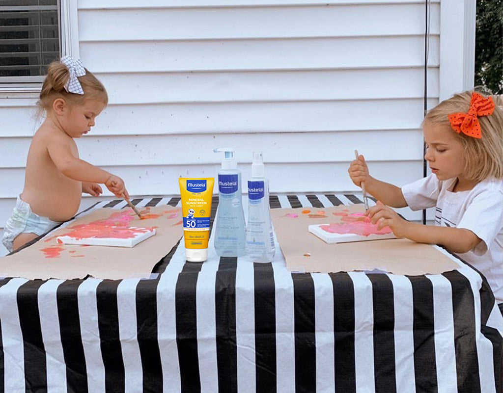 two kids painting outside while being protected by mustela sunscreen products