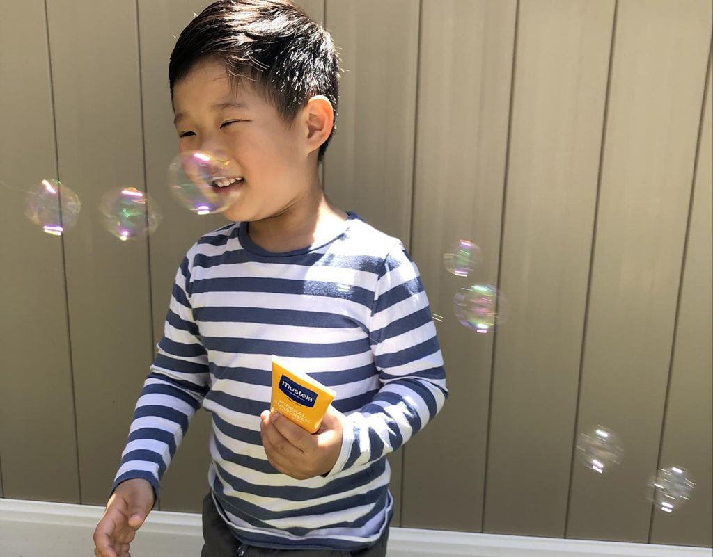 Kid playing with bubbles while using mustela sunscreen