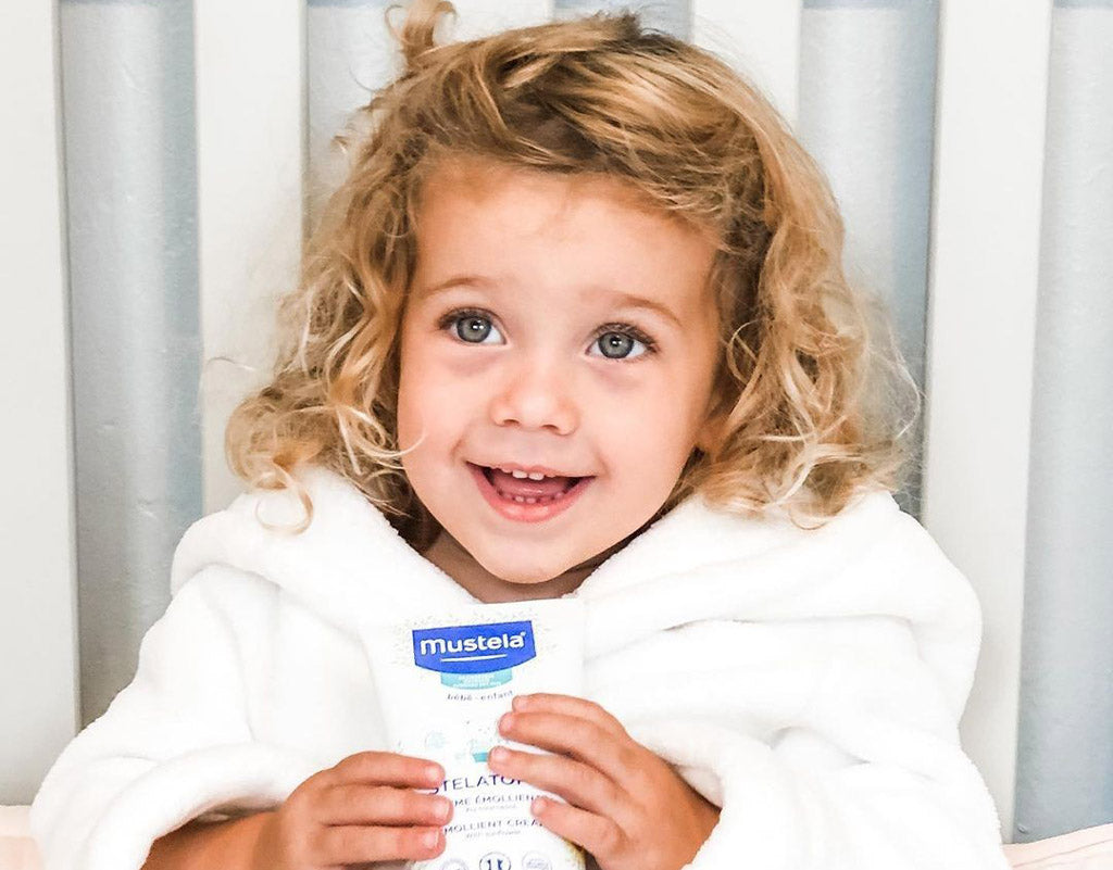 Child holding Mustela products that fight all types of eczema
