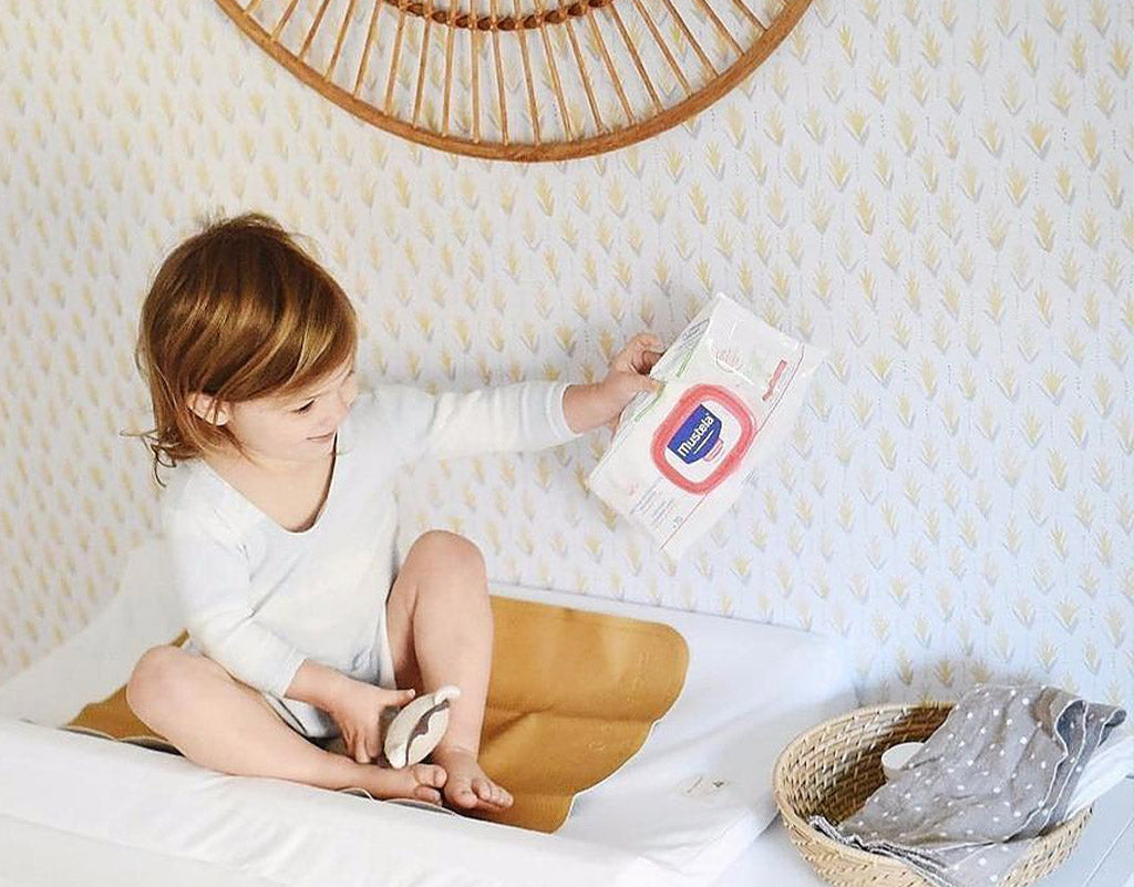 young girl sitting on diaper changing table