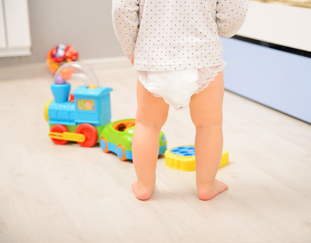 Kid in diaper about to play with toys