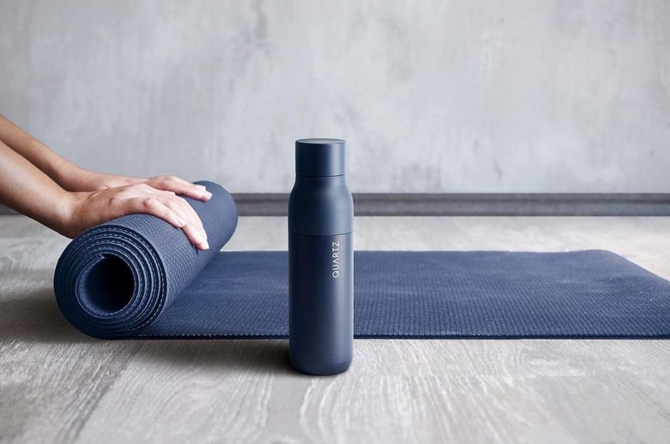 Woman rolling up a yoga mat behind a LARQ water bottle