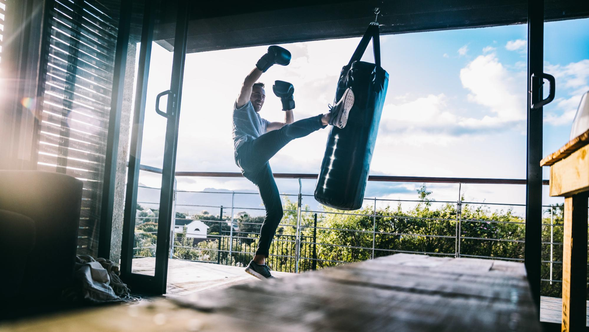 Young man jumping and kicking a punching bag