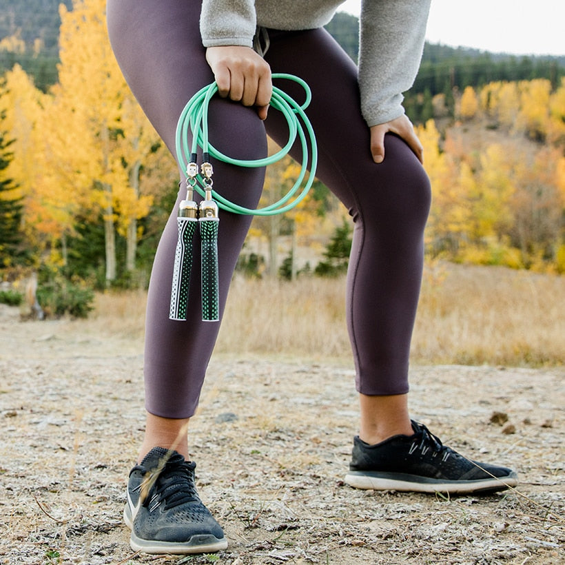 Woman outside in running shoes holding 1/4 LB ropes with Slim handles