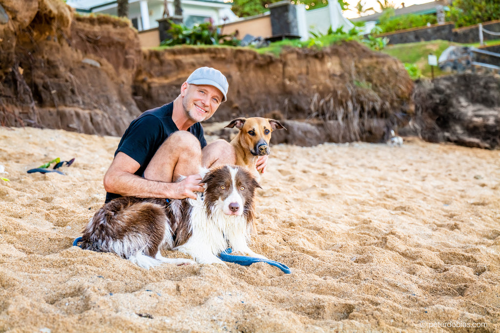 Dr. Peter Dobias with his border collie Pax sitting on a beach