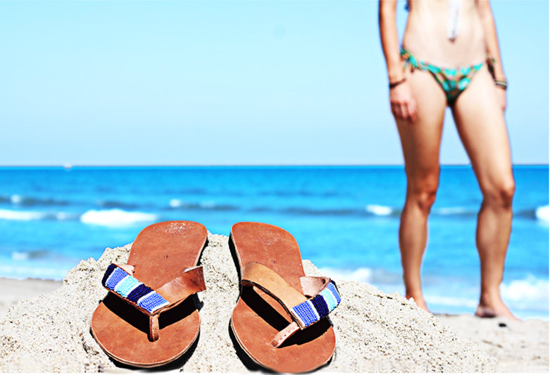 Blue Ribbon Sandals on Beach. Fair trade accessories ethically handmade by empowered artisans in East Africa.