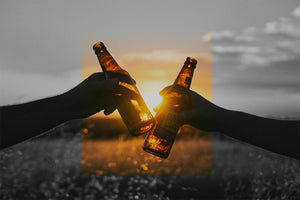 Two people toasting with beverages behind a sunset in a field