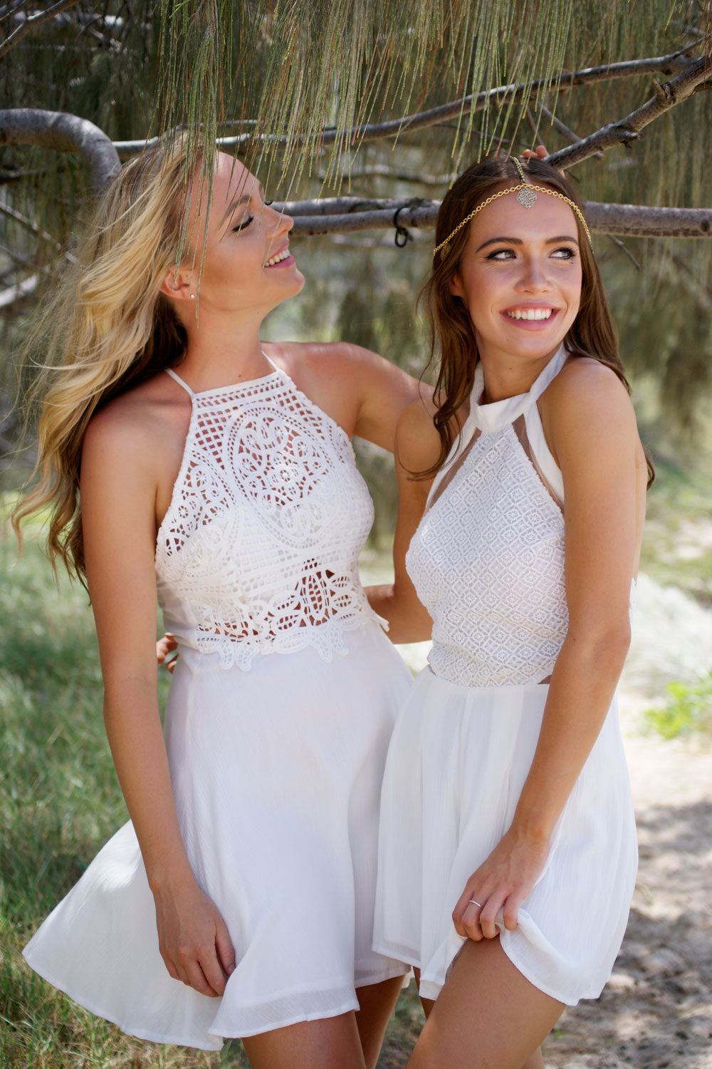Two models standing under a tree modelling white lace garments