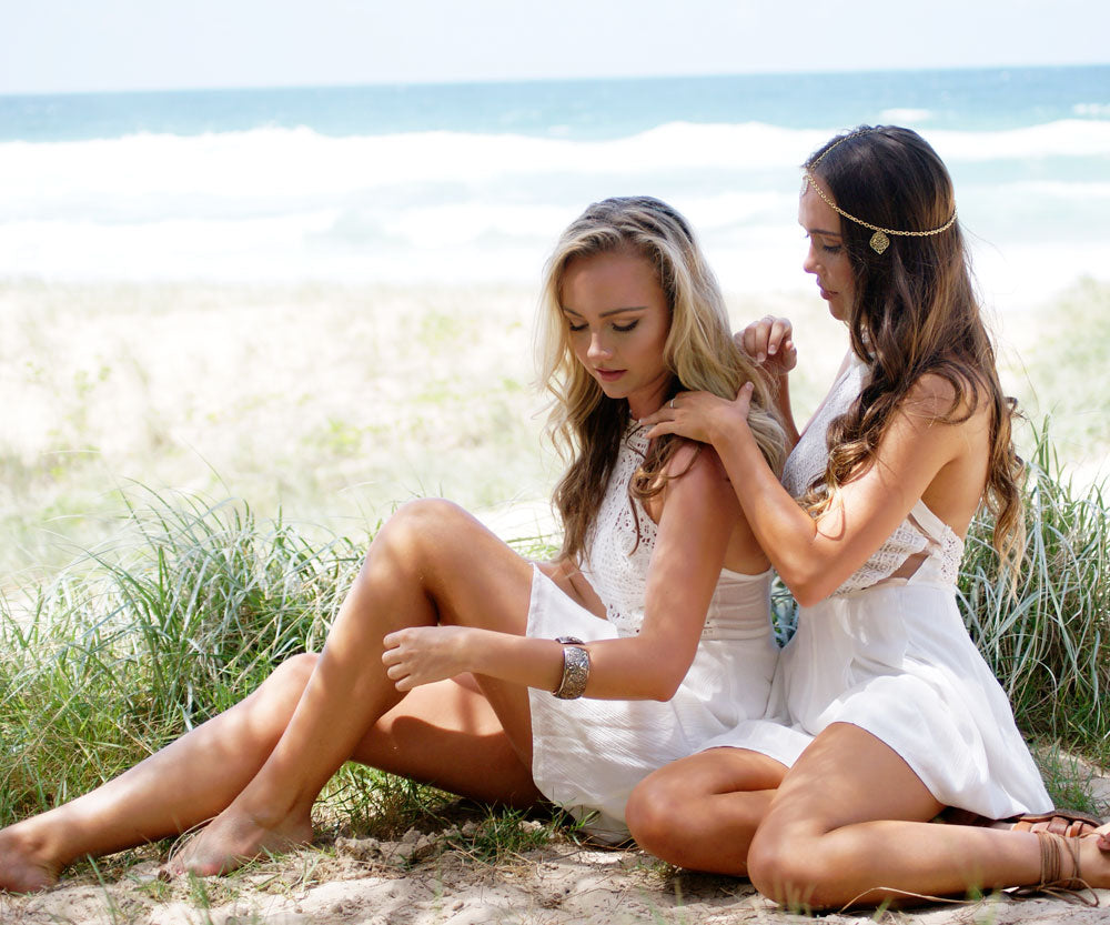 Models sitting together on sand