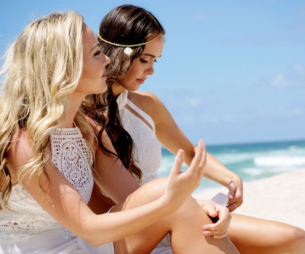 Two models sitting in sand for White Lace Lookbook