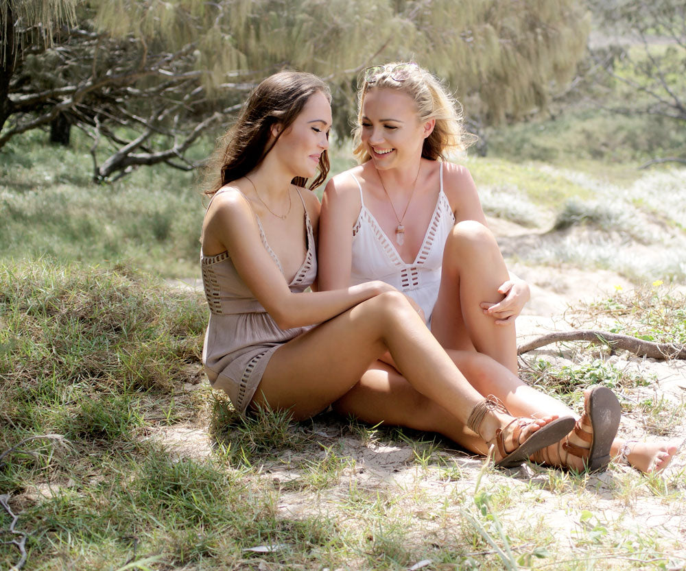 Both models sitting, wearing Indiana Playsuit