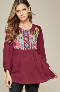 Babydoll top with round embroidered neckline and 3/4 sleeves.